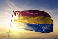 La Romana Province of Dominican Republic flag textile cloth fabric waving on the top sunrise mist fog. Beautiful stock image