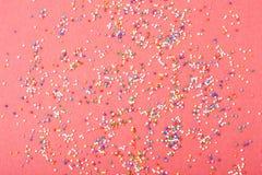 La ronda colorida asperja derramado en el fondo rojo, aislado Foto de archivo libre de regalías