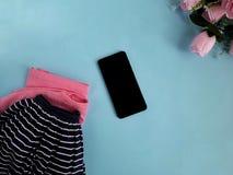 La ropa brillante del color, subió camiseta, falda de lino de la marina de guerra, teléfono, flores en fondo azul fotografía de archivo libre de regalías