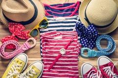 La ropa colorida y los accesorios a vestirse arreglaron en una tabla de madera Fotos de archivo libres de regalías
