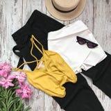 La ropa de las mujeres con las flores en un fondo de madera imagen de archivo