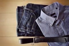 La ropa de los hombres descompuesta en un fondo de madera Fotos de archivo