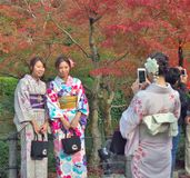 La ropa de mujer joven un vestido tradicional llamado Kimono es tomada una foto por su amigo Imagenes de archivo