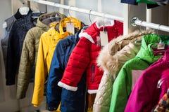 La ropa del bebé cuelga en un estante en una tienda del diseñador foto de archivo libre de regalías