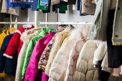 La ropa del bebé cuelga en un estante en una tienda del diseñador fotos de archivo
