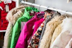 La ropa del bebé cuelga en un estante en una tienda del diseñador fotografía de archivo libre de regalías