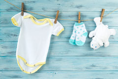 La ropa del bebé y el oso blanco juegan en una cuerda para tender la ropa imagen de archivo