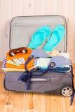 La ropa, los zapatos y las tabletas para el viaje son listos y mentira en un sui Imagen de archivo