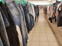 La ropa pesa en suspensiones en una tienda de segunda mano Vaqueros y blusas baratos de compra a partir de la segunda mano en la  foto de archivo