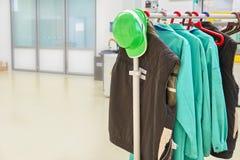 La ropa protectora y el casco de seguridad verde en una capa atormentan en la fábrica Foto de archivo libre de regalías