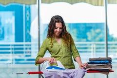 La ropa que plancha de la mujer joven a bordo fotos de archivo libres de regalías