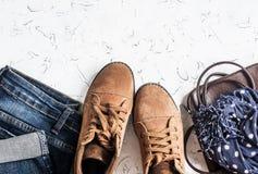 La ropa y accesorios - botas del ante, vaqueros, bolso de cuero, bufanda de las mujeres En un fondo ligero Imagen de archivo