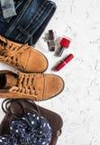 La ropa y accesorios - botas del ante, vaqueros, bolso de cuero, bufanda, esmalte de uñas rojo y lápiz labial de las mujeres Imagen de archivo libre de regalías