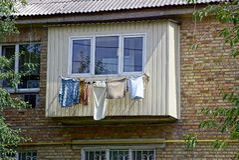 La ropa y el lavadero se seca después de lavarse cerca del balcón en la pared de la casa imagen de archivo libre de regalías