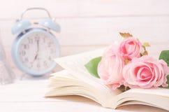 La rosa artificial en colores pastel y el libro abierto con el vintage entonan fotos de archivo