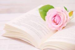 La rosa artificial en colores pastel y el libro abierto con el vintage entonan imagen de archivo