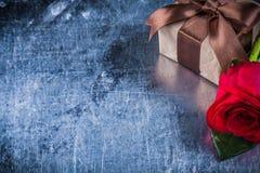 La rosa naturale ha imballato il contenitore di regalo su fondo metallico graffiato co Immagini Stock
