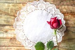 La rosa rossa del germoglio su fondo dei tovaglioli bianchi openwork Immagine Stock