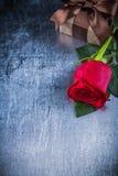 La rose augmentée a enveloppé le giftbox avec l'arc sur le CCB métallique rayé Image libre de droits