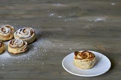 La rose délicieuse et par bonbon cuite au four a formé la pâtisserie avec de la garniture d'aux pommes du plat blanc sur le fond  Photos libres de droits