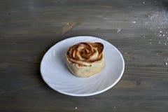 La rose délicieuse et par bonbon cuite au four a formé la pâtisserie avec de la garniture d'aux pommes du plat blanc sur le fond  Images libres de droits