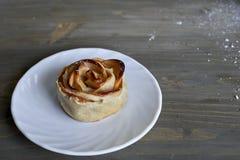 La rose délicieuse et par bonbon cuite au four a formé la pâtisserie avec de la garniture d'aux pommes du plat blanc sur le fond  Image libre de droits