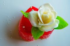 La rose de blanc avec le vert part sur un coeur rouge de confiture d'oranges, des bonbons pour des amants et des mariages image libre de droits