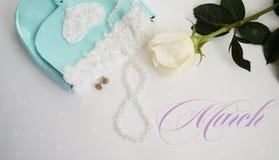 La rose de blanc, les boucles d'oreille vertes et la turquoise mettent en sac sur un fond blanc Photos stock