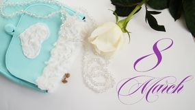 La rose de blanc, les boucles d'oreille vertes et la turquoise mettent en sac sur un fond blanc Photographie stock libre de droits