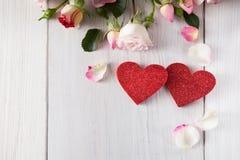 La rose de rose fleurit des pétales et des coeurs en bois faits main de scintillement sur le bois rustique blanc Photographie stock libre de droits