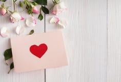 La rose de rose fleurit et carte de papier faite main avec le coeur sur le bois rustique blanc Photo stock