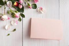 La rose de rose fleurit les pétales et la carte de papier faite main sur le bois rustique blanc Images libres de droits