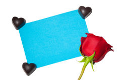 La rose de rouge avec la carte et le coeur forment le chocolat d'isolement sur le blanc Image libre de droits