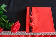 La rose de rouge de décor de mariage se trouve sur la table et le livre de souhait pour les nouveaux mariés photo stock
