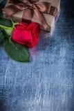 La rose de rouge a enveloppé le giftbox avec l'arc sur le backgrou métallique rayé Images libres de droits