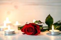 La rose de rouge est parmi les bougies allumées Photos libres de droits