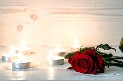 La rose de rouge est parmi les bougies allumées sur la surface blanche en bois Image stock
