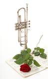 La rose de rouge et la vieille musique de feuille de notes sonnent de la trompette Photo stock