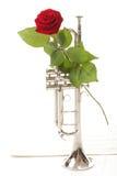 La rose de rouge et la vieille musique de feuille de notes sonnent de la trompette Photographie stock