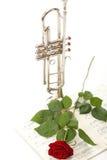 La rose de rouge et la vieille musique de feuille de notes sonnent de la trompette Image libre de droits