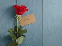 La rose de rouge sur la table en bois bleue a tiré de ci-dessus pour le 8 mars Images stock