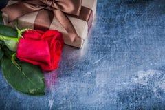 La rose naturelle de rouge a enveloppé le boîte-cadeau sur le backgrou métallique rayé Image libre de droits