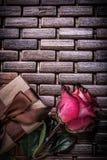 La rose parfumée rouge a enveloppé le giftbox sur en bois en osier Photographie stock libre de droits