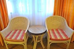 La rota relaja sillas y la mesa redonda cerca de la ventana Imagen de archivo