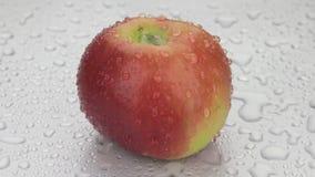 La rotación, descensos del agua cae en una manzana roja madura almacen de video