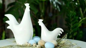 La rotación, la composición festiva de Pascua en los rayos de la luz, en la paja, allí es dos figurillas blancas de gallina y metrajes