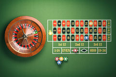 La roue de roulette de casino avec le casino ébrèche sur la table verte jeu Photo stock