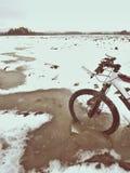 La roue de vélo de montagne a divisé par la glace en eau Appréciez l'hiver faisant du vélo avec l'amusement images libres de droits