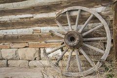 La roue de vintage sarcle le rondin et le mur en pierre Photographie stock