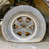 La roue est abaiss?e en cons?quence de l'inactivit? des pneus de voiture, d'?ge, de coupe ou de piq?re Travail de pneu images libres de droits